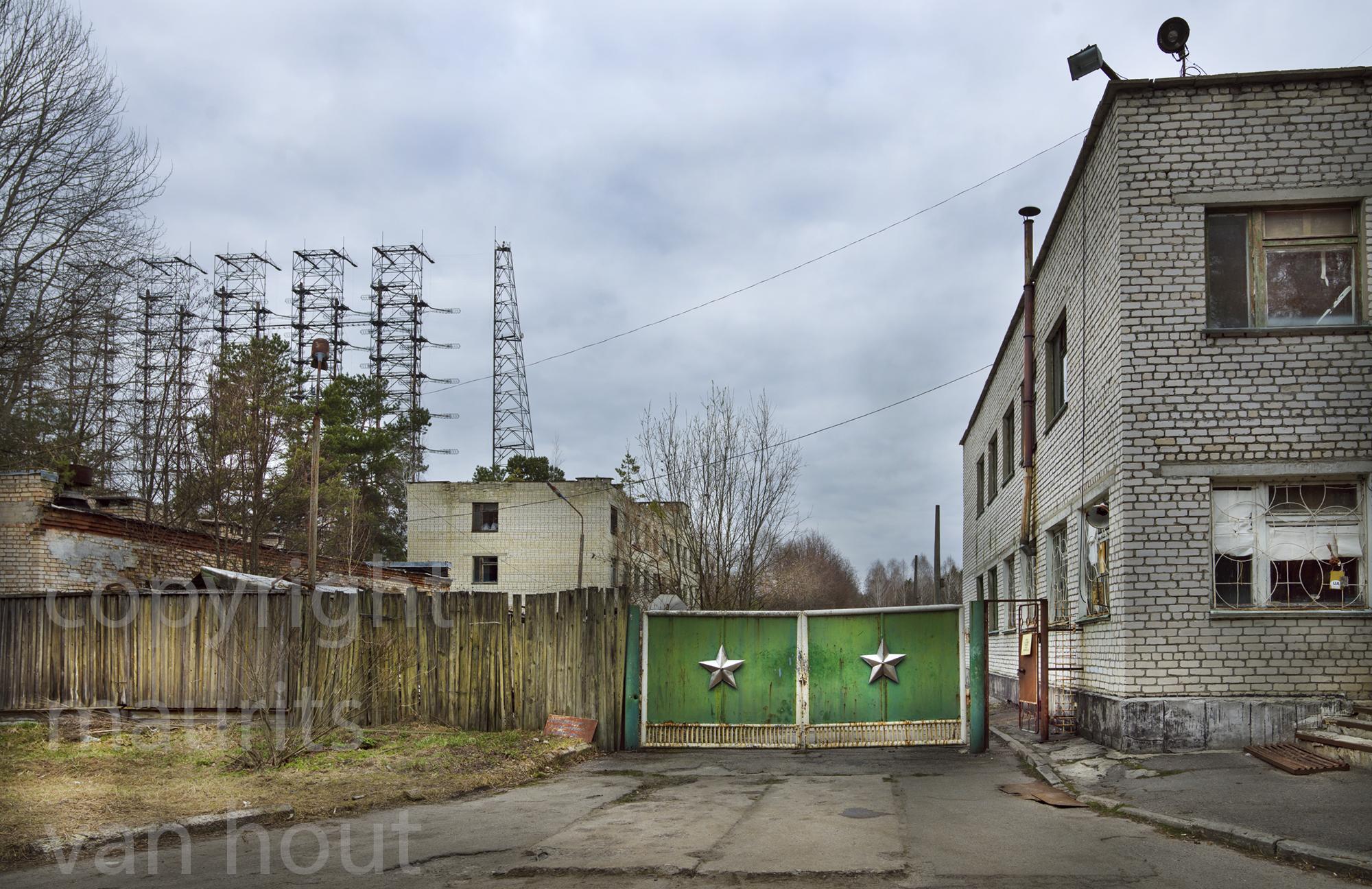 Tjernobyl 2 bestond uit een ministadje met daarbij een enorme installatie de Duga of Doega. In de Koude Oorlog gebruikt door de Sovjet Unie. Het wordt gezegd dat eenderde van de stroomproductie van Tjernobyl geproduceerd werd voor deze installatie. Op de foto de toegangspoort naar het complex van de Duga.